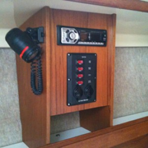New teak cabinet on port side.  Holds original chart light, new secondary DC panel and AM/FM radio w/ CD player.
