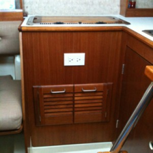 Refinished galley with GFI shore power and louvered teak doors in under stove locker.